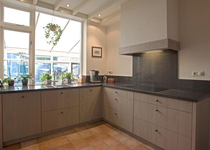 Keuken Zwart Met Hout : schouw met inbouw afzuigunit bevindt zich een middelhoge kastwand met